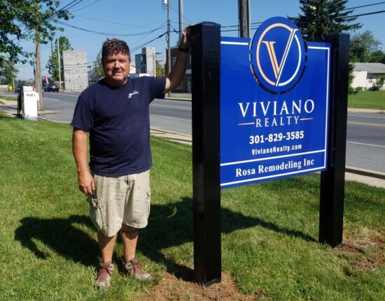 DMS Sign connection installer stands next to Viviano Realty Post and Panel Sign