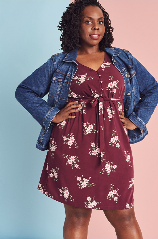 plus size woman in denim jacket and floral dress