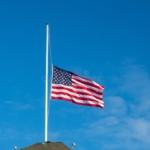 american-flag-half-staff-against-blue-sky-flies-s-sunny-windy-day-133895458