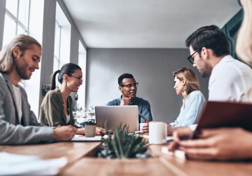 Grupo de jóvenes modernos en ropa casual elegante discutiendo negocios mientras trabaja en la oficina creativa