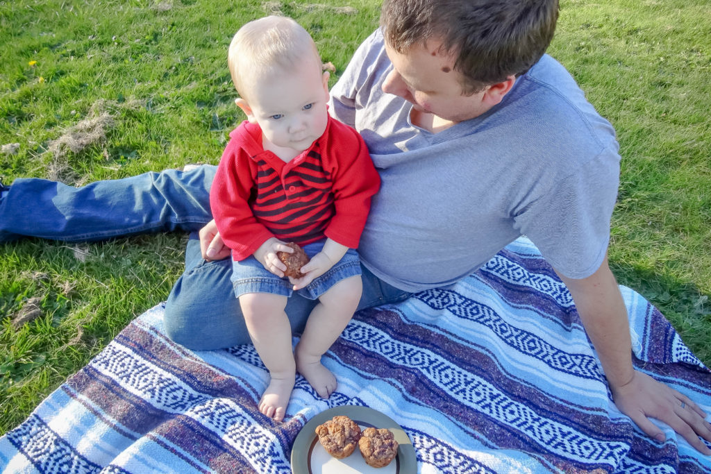 Toddler boy sitting on dad's lap on a picnic blanket holding a muffin with a plate of muffins in front of them