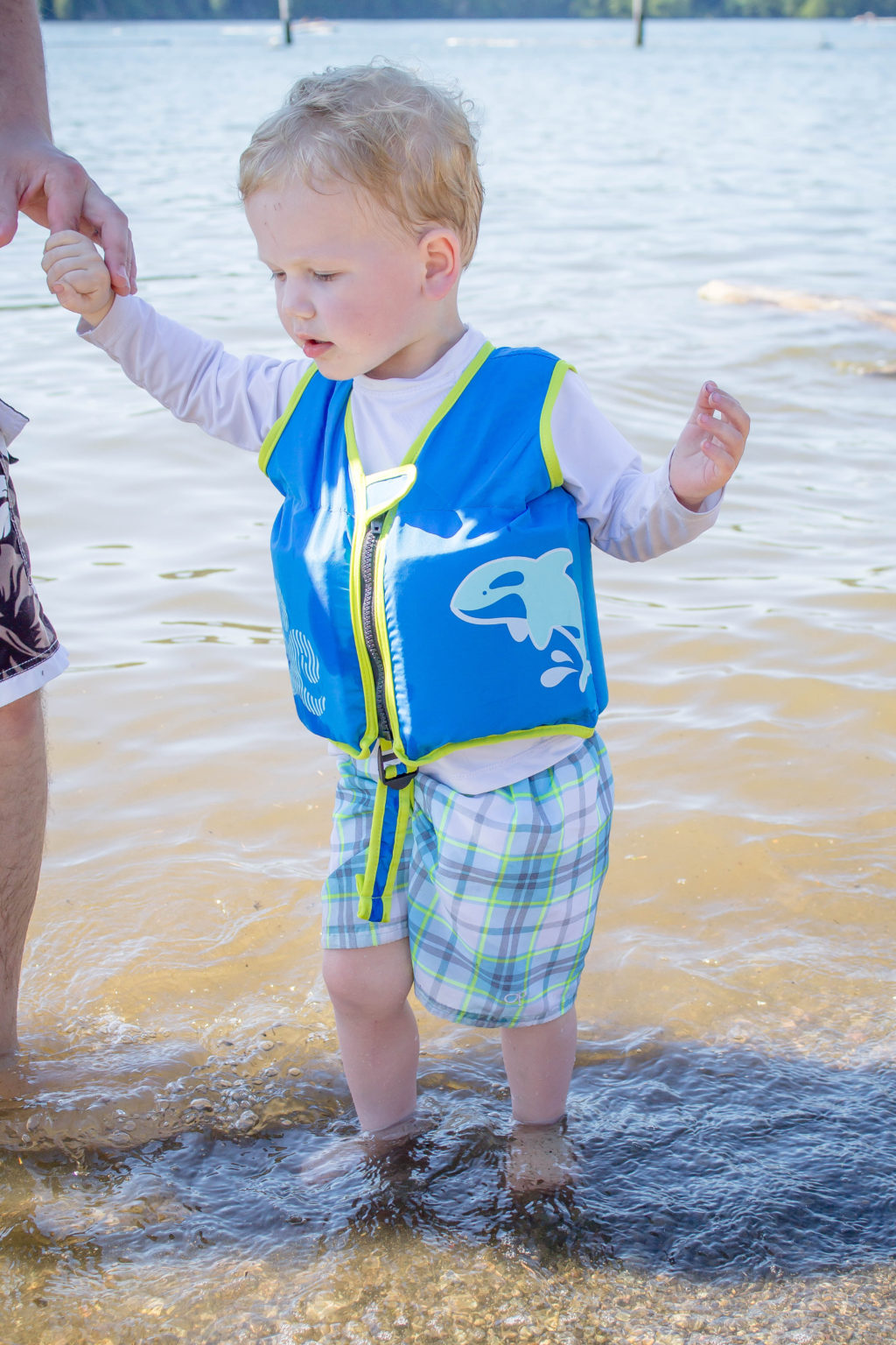 Toddler boy wearing SwimWays vest wading in water while holding man's hand