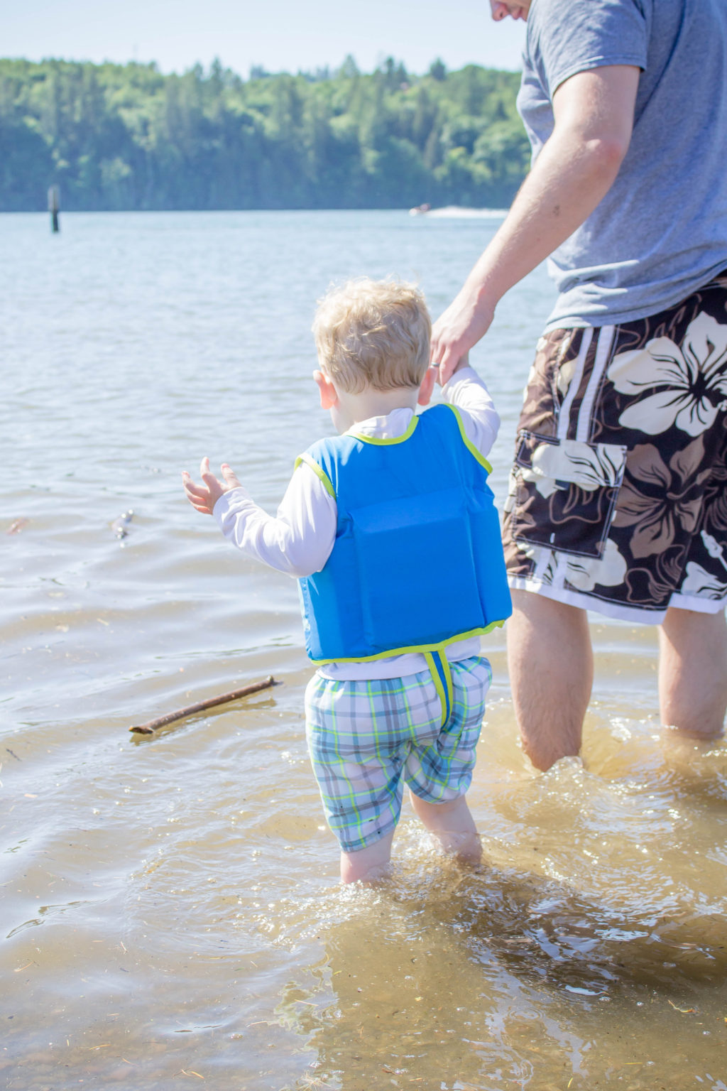 Toddler boy wearing SwimWays vest holding man's hand while walking away in the water