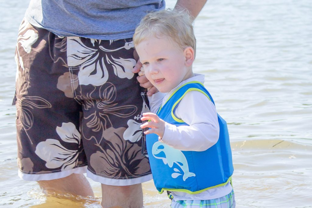 Toddler boy wearing a SwimWays flotation device in water, holding dad's hand