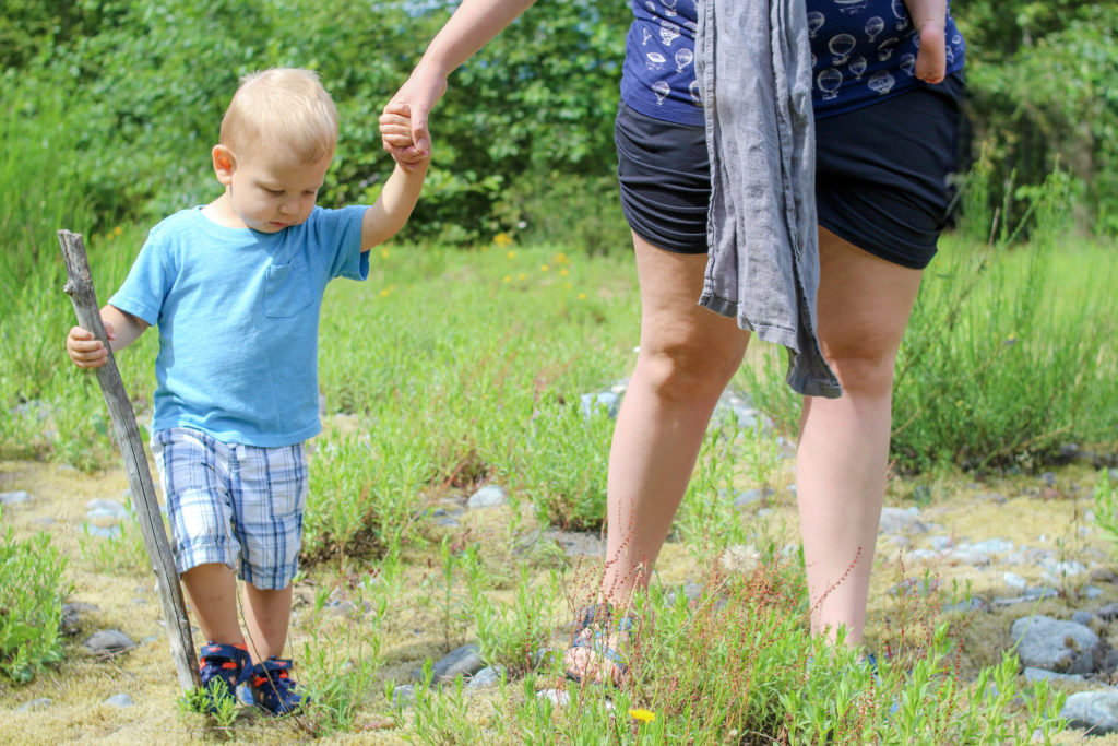 Closeup of toddler boy holding a woman's hand. All you can see of the woman is her legs.