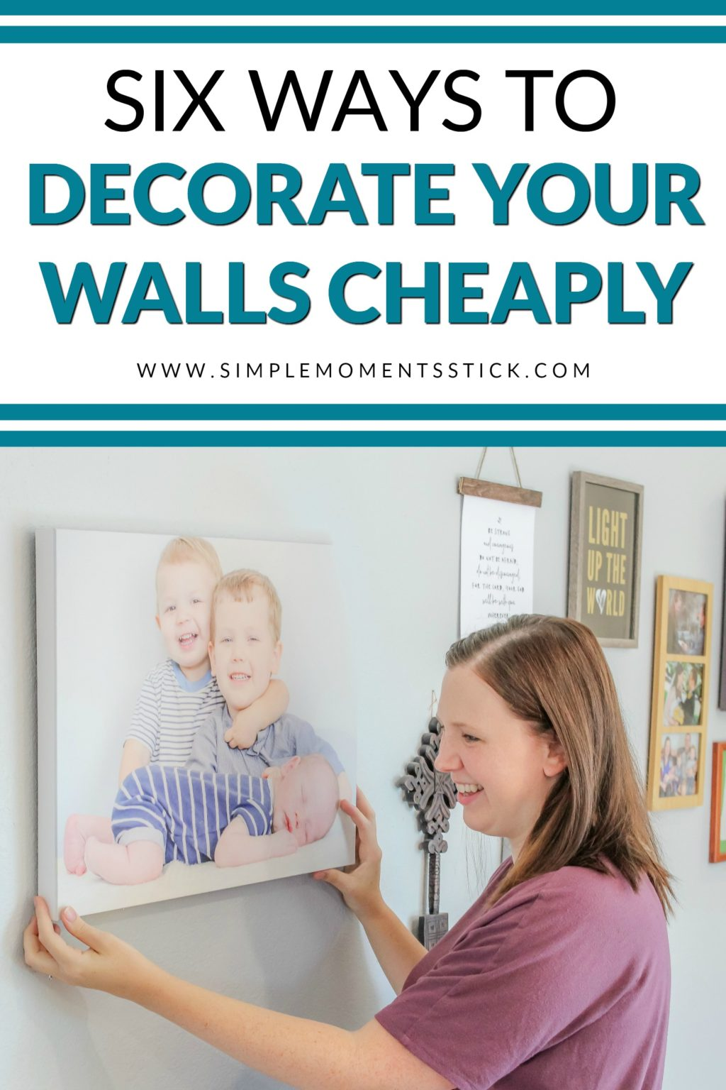 Woman hanging canvas picture of two young boys and a newborn baby with text - Six Ways to Decorate Your Walls Cheaply