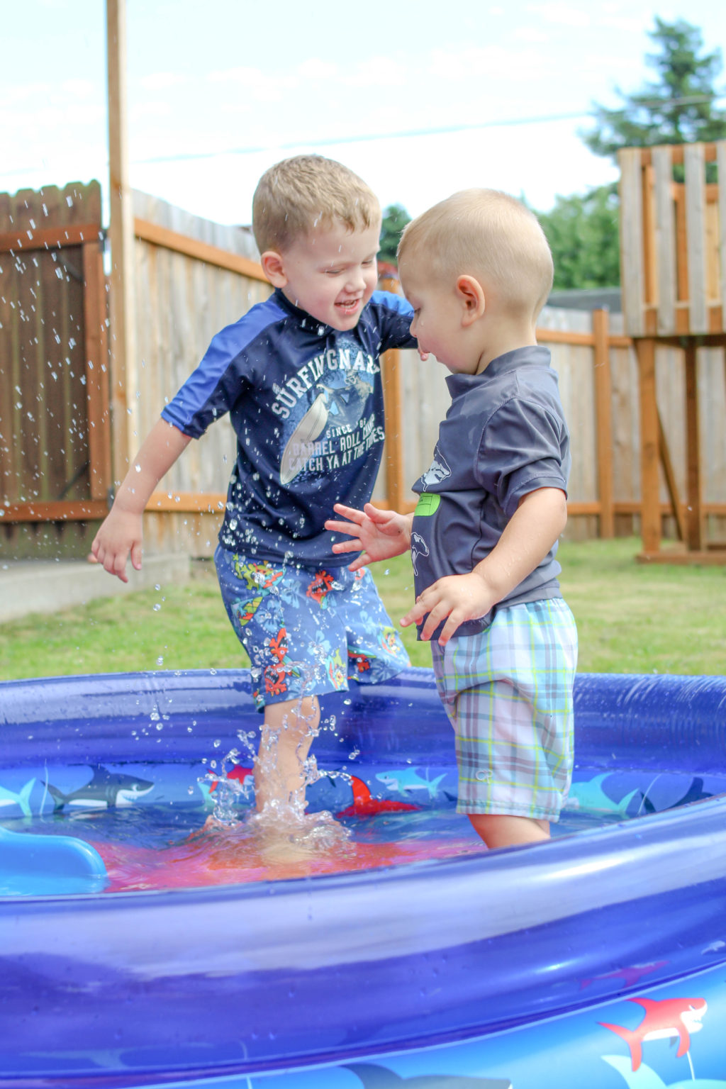 Preschooler boy splashing into a wading pool with toddler boy looking surprised