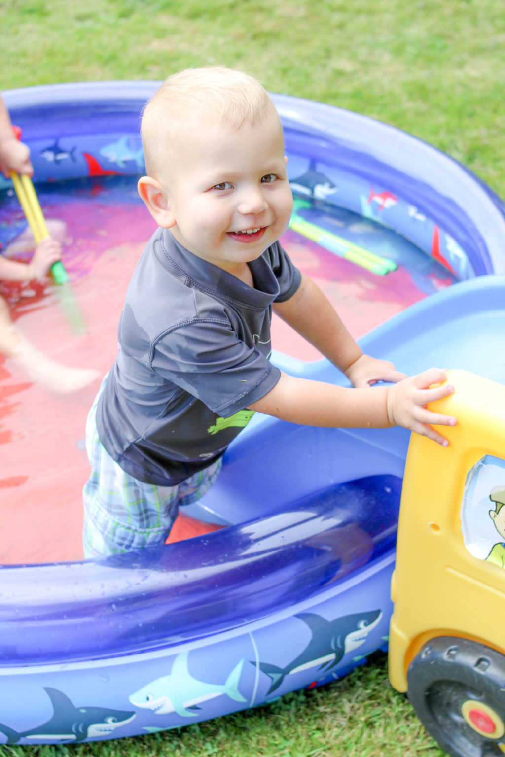 Blond toddler boy standing in wading pool while holding onto the side of a small slide and smiling at the camera