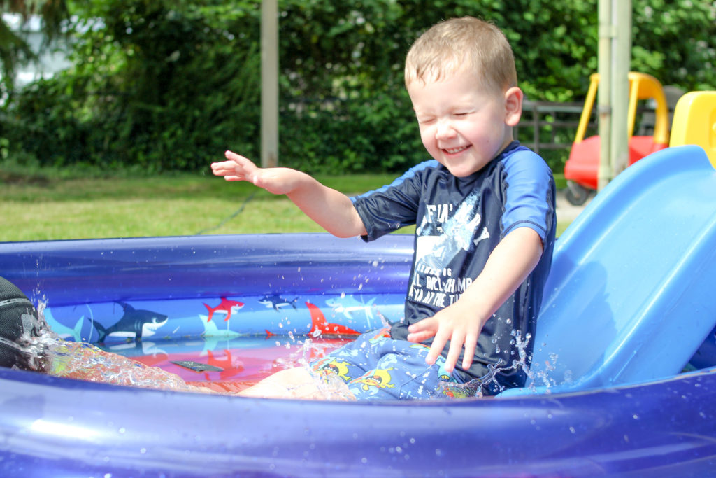 Preschooler boy sliding down small slide into wading pool while closing his eyes tightly