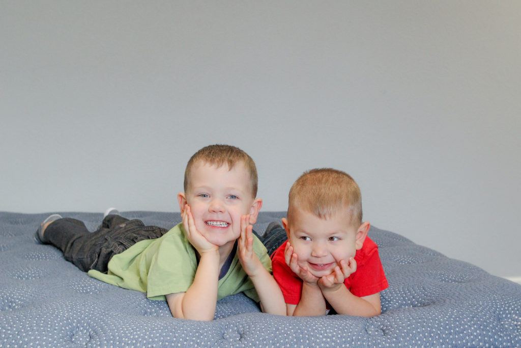 Two boys on mattress.  Best sleep tips for parents. Getting better sleep with a newborn baby.  How to prevent sleep deprivation