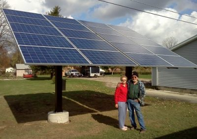Customers standing in front of their solar array on pole mounts