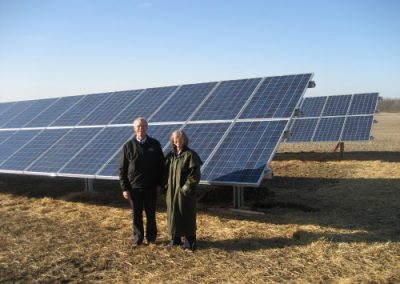 Customers standing next to 18 kW ground mount on a local farm