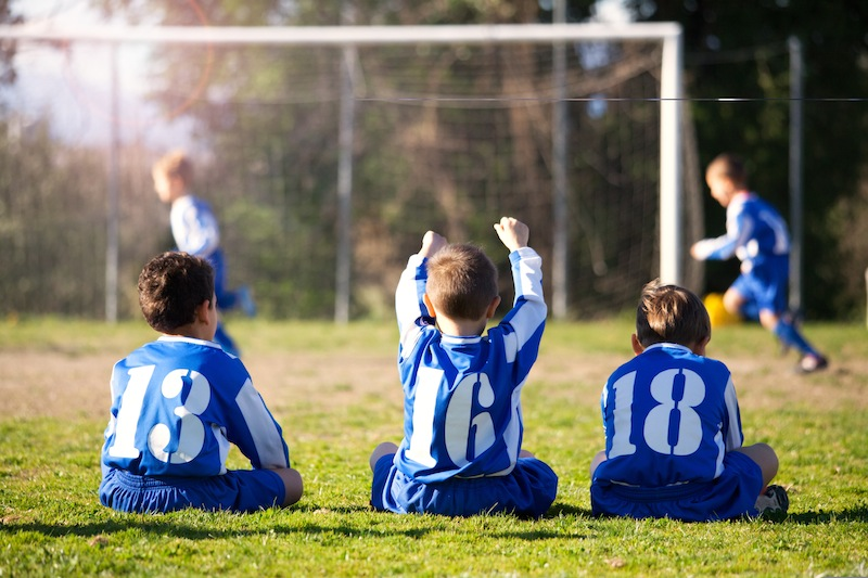 young boys in uniform watching their team while playing football