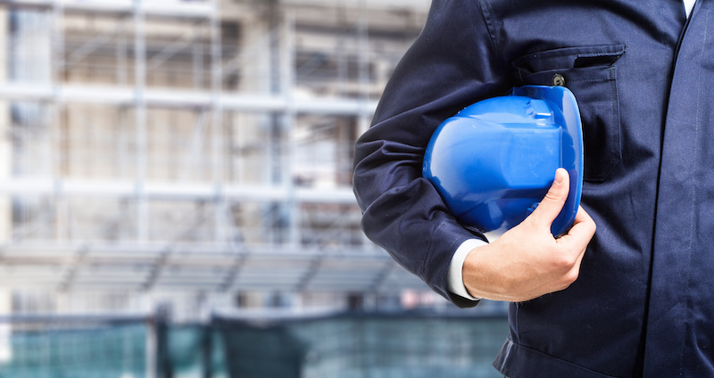 occupational medicine - worker holding his helmet in front of a construction site