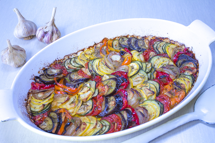 The roasted Tian with thinly cut,  layered vegetables,  sliced garlic,  extra virgin olive oil and rosemary