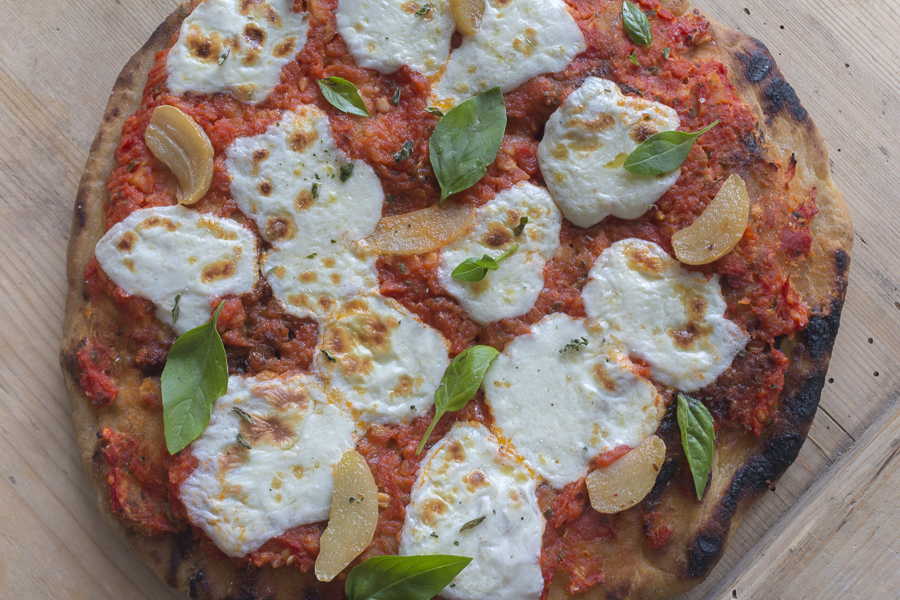 Top the pizza with Raw Sauce,  Fresh Mozzarella,  Sliced Cooked Garlic and Basil Leaves