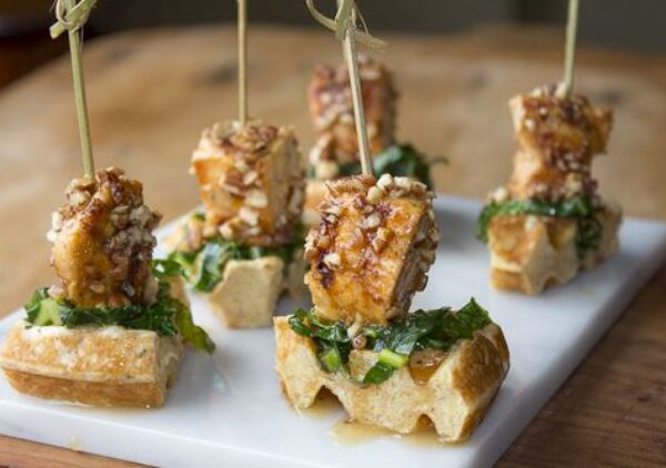 """Sautéed Collard Greens top these buttermilk waffles and are topped with """"grilled pecan chicken"""" for the ultimate appetizer"""