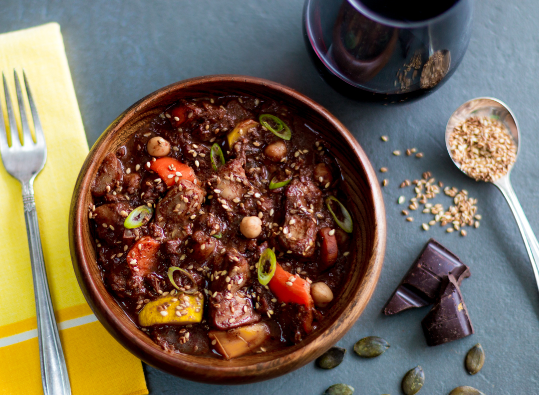 A Mexican style rich stew with chicken, lots of vegetables, spices, tomatoes, chiles, sesame seeds, cocoa powder and bittersweet chocolate.