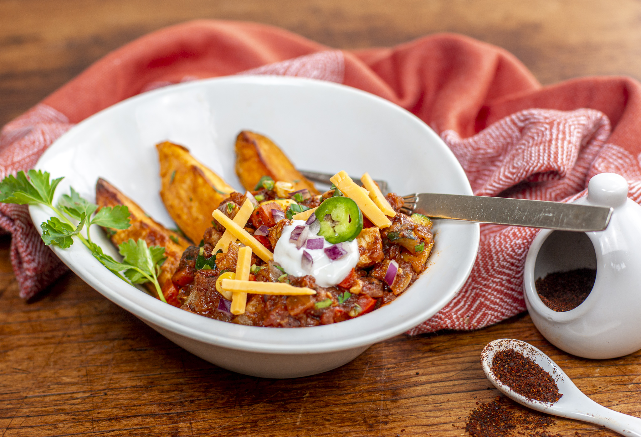 A bowl of Tempeh Chili in a bowl over roasted sweet potato wedges with toppings