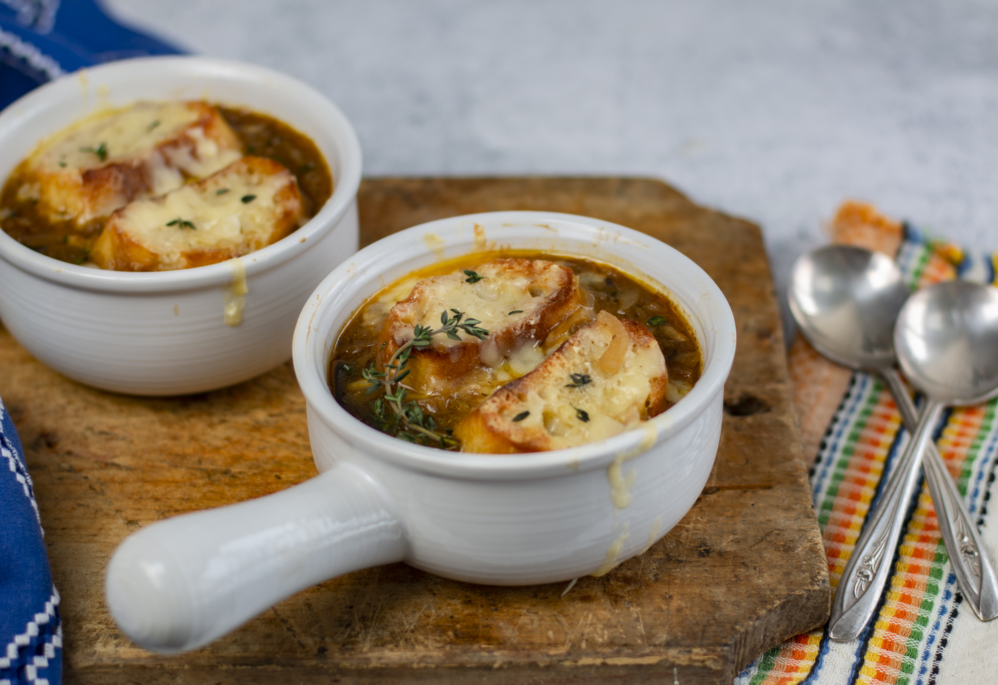 Two white modern crocks with French Onion Soup with Fresh Thyme.