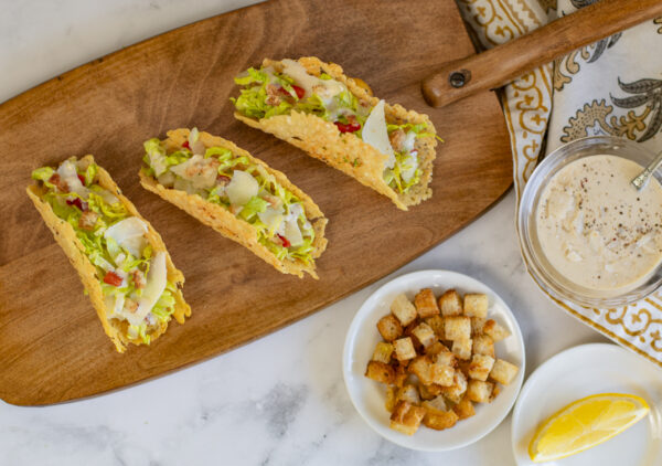 Three Caesar Salad Tacos in Parmesan Crisp Shells on a vintage wood serving board