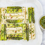 Grilled Asparagus & Hearts of Palm in a quilted pattern with Chimichurri Sauce on a vintage white plate