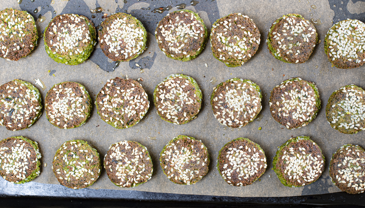 Add cooked falafel to a parchment line rimmed baking pan to finish in the oven