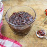 Karen's Tomato Jam with Shallots - Less Sugar in a glass bowl on a vintage wooden board