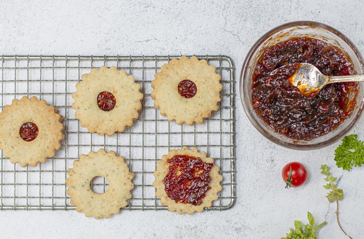 Savory Cheese Linzer Thins sandwiched with Tomato Jam on a vintage wire rack