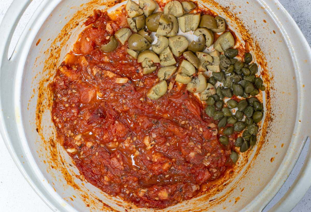 Tomatoes, Olives and Capers cook in a heavy pot