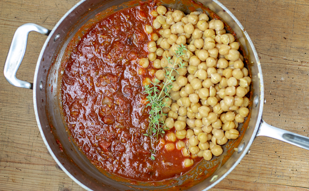 Chickpeas are added to the sauce base, simmered then baked