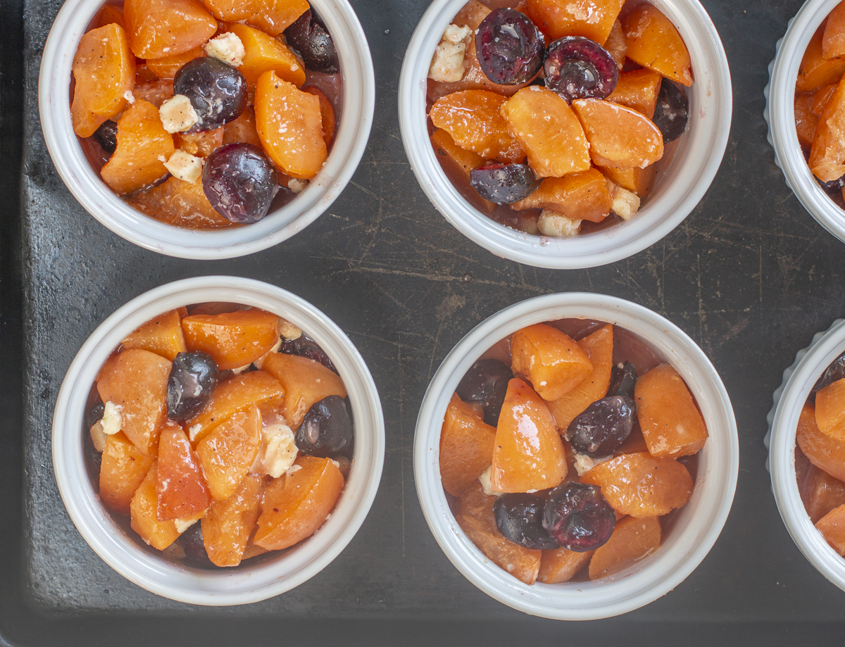 Portioning the fruit into six ramekins: Apricot-Cherry Cobblers