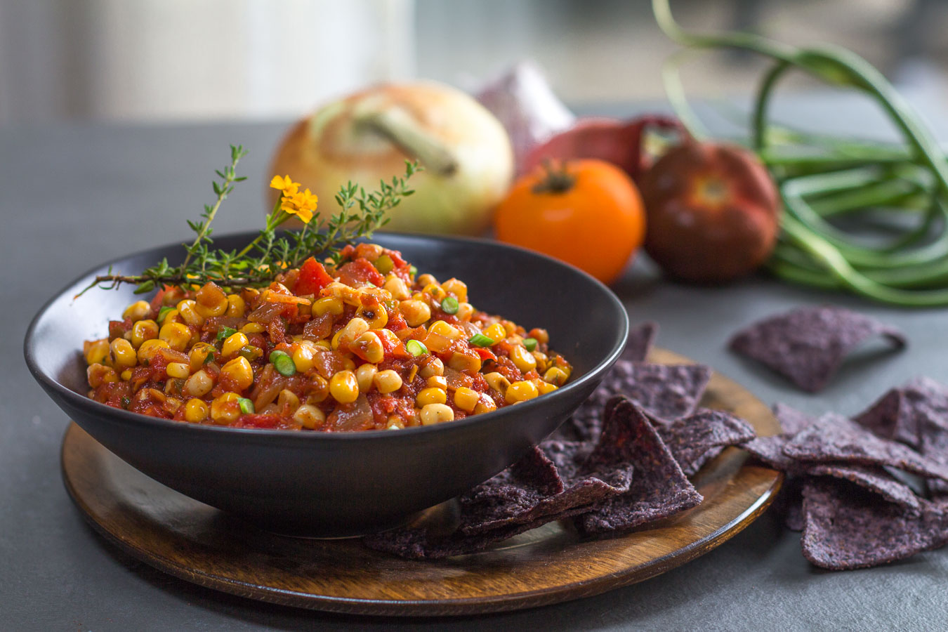 Fresh Corn and Roasted Tomato Salsa in a black bowl