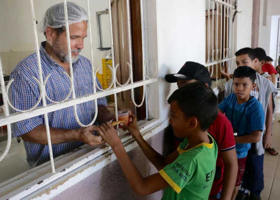 A volunteer distributes food to the children.