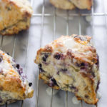 Blueberry Scones on a cooling rack drizzled with a Greek yogurt lemon glaze.