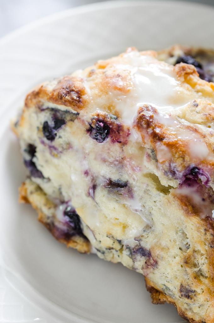 Close up shot of a blueberry scone drizzled with lemon-yogurt glaze.