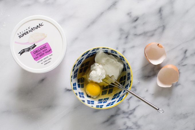 Greek yogurt, maple syrup, and and egg in a small blue bowl.