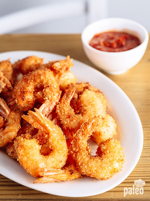 Platter of fried coconut shrimp with dipping sauce in the background.