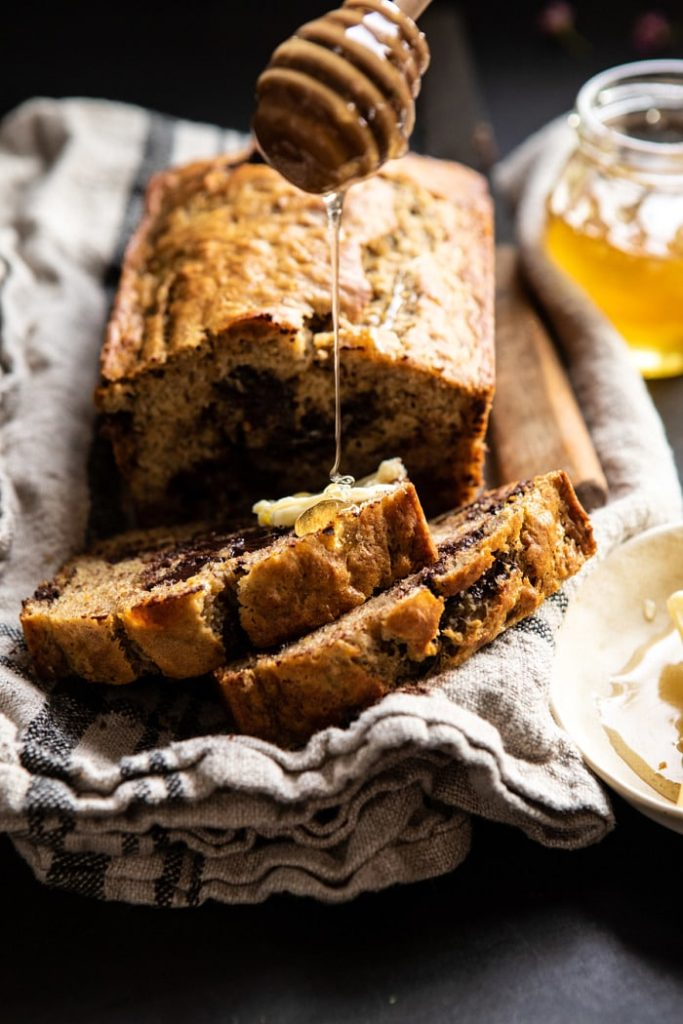 Slices of banana bread being drizzled with honey.