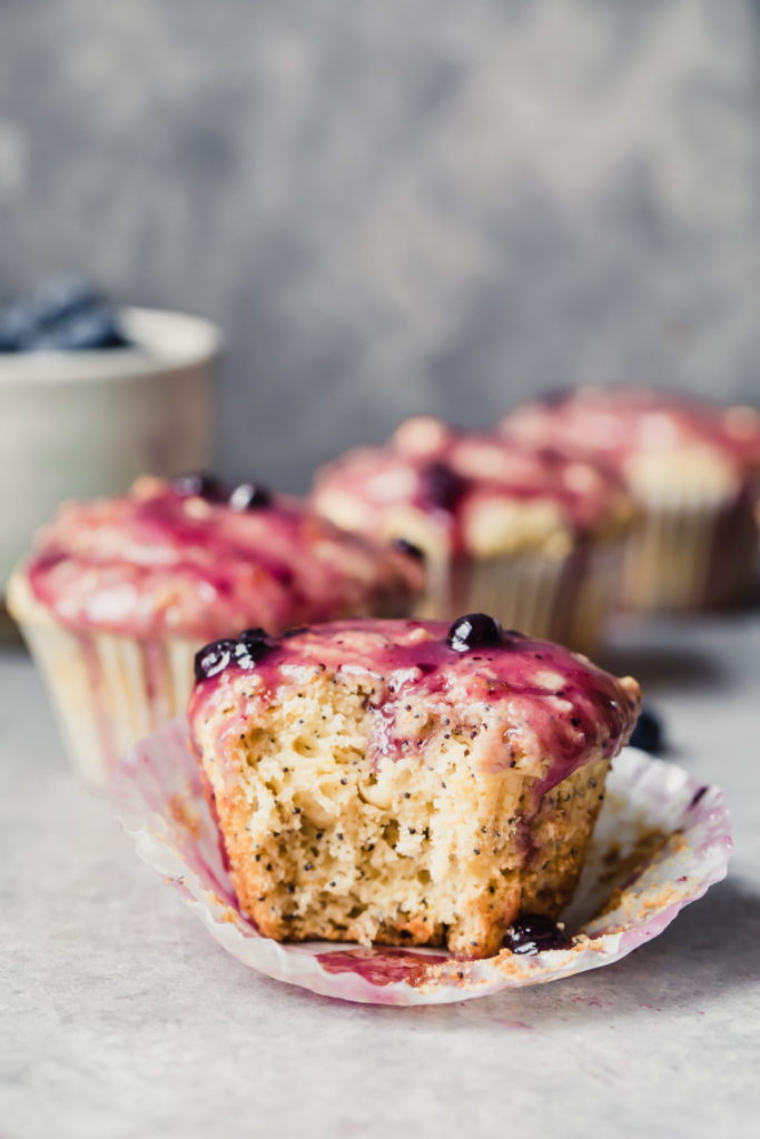 Photo of a lemon poppyseed muffin with a bite taken out of it.