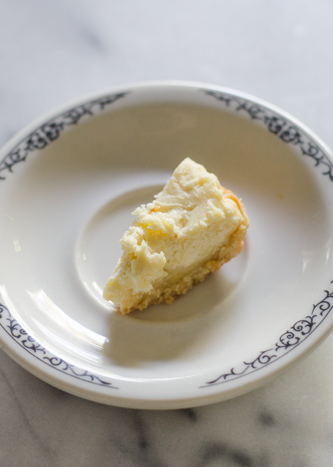 A very small piece of cheesecake on a small plate.