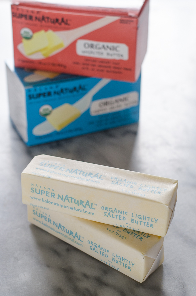 Sticks of Kalona SuperNatural butter on a marble surface with packaging in the background.