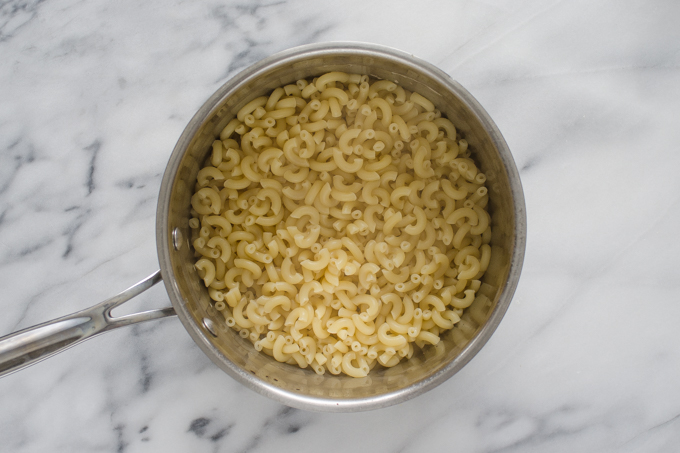 Cooked macaroni noodles in a stainless steel pot on a marble surface.