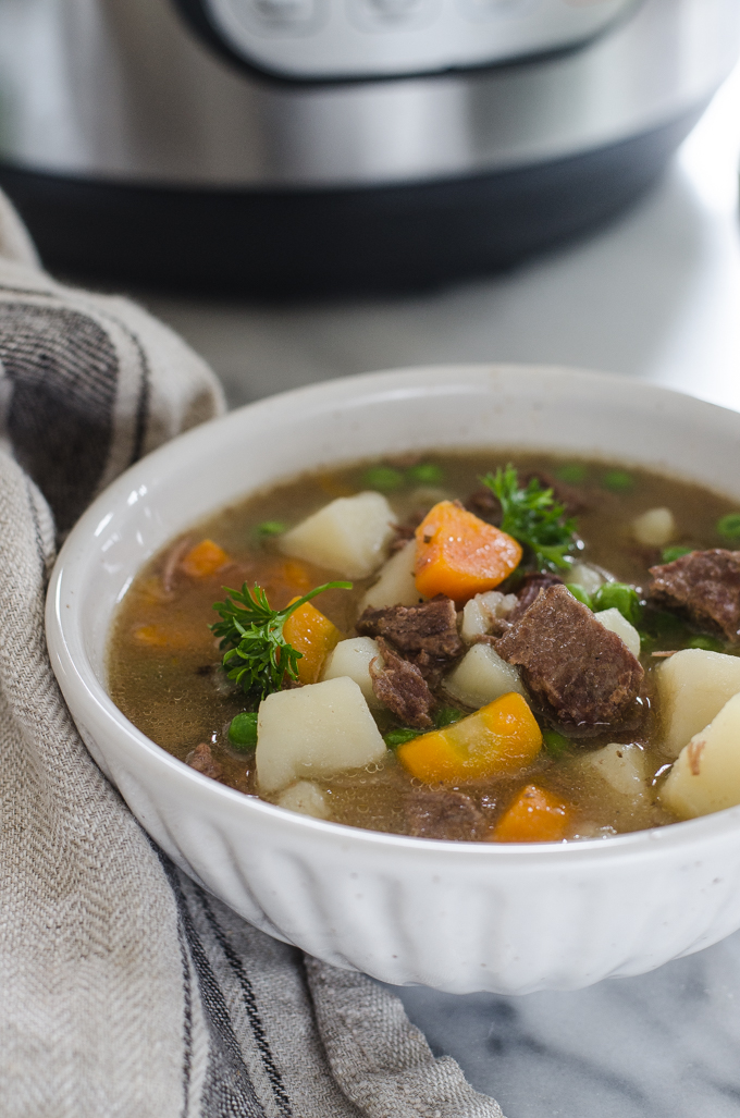 A bowl of Instant Pot Beef Stew with the pressure cooker in the background.