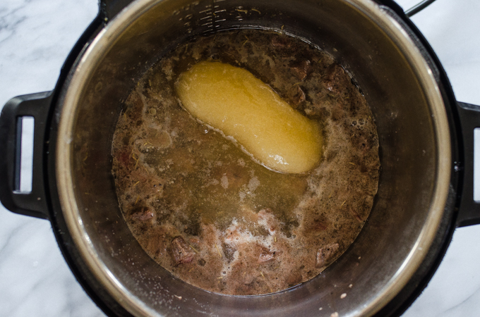 Adding the broth to the Instant Pot.