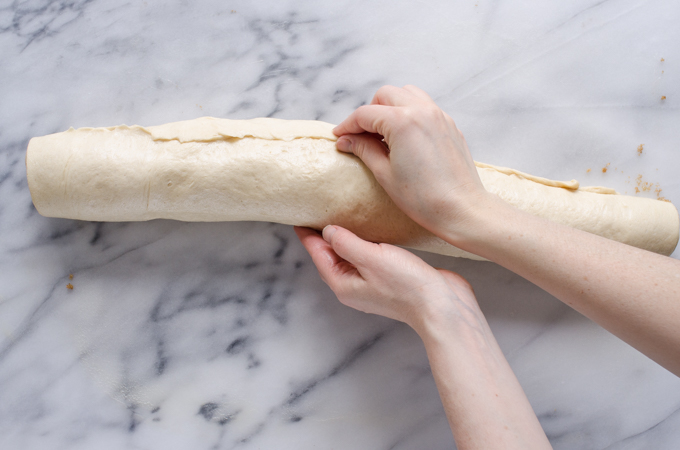 Pinching the seam of the rolled up dough.