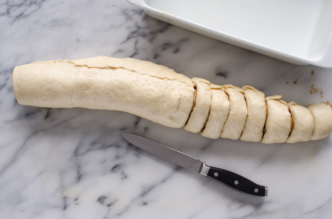 Slicing the log of dough into rolls.