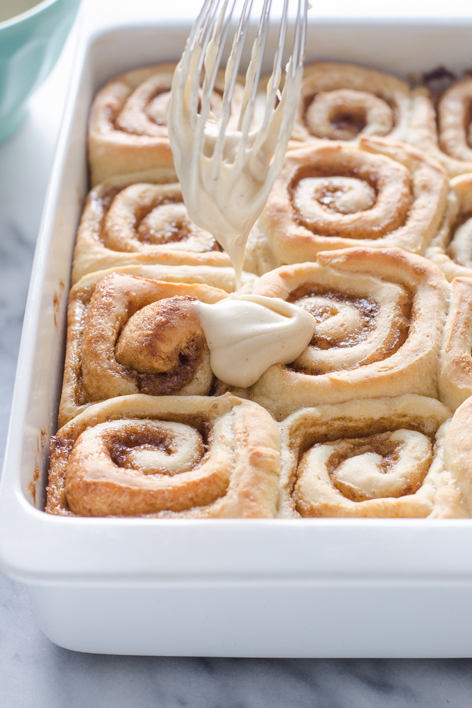 Adding the brown butter frosting to the rolls with a whisk.