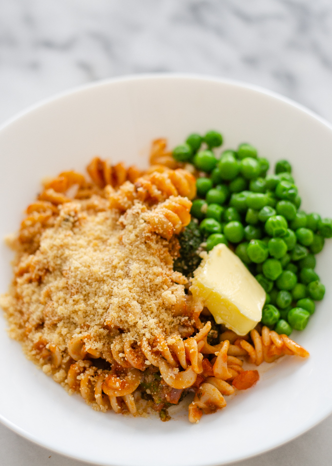 Leftover spaghetti and green peas in a bowl topped with butter and parmesan cheese.