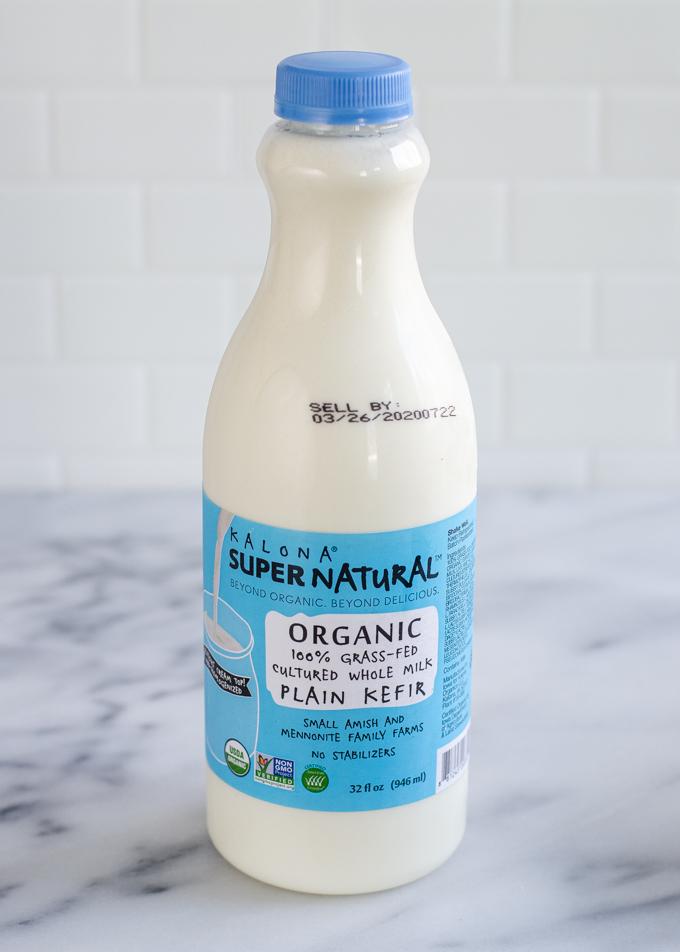 A bottle of Kalona SuperNatural kefir on a marble surface.
